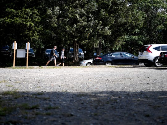 A pair walk past a gravel parking lot on Banks Avenue which charges for parking after 7 on weekdays and on the weekend but is private otherwise.