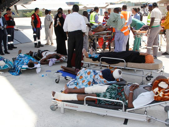 Critically wounded people wait to be moved into a waiting