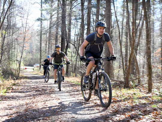 From left: Heather Maharrey, Jeff Maharrey, and Tait Wilson, all of Nashville, take off on a mountain biking trip at Bent Creek Experimental Forest on Friday, Nov. 17, 2017.