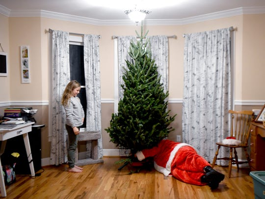 Kenzie Robinson helps Santa determine if her family's Christmas tree is straight as he make adjustments to the stand during a delivery to their home on Sunday, Nov. 19, 2017.