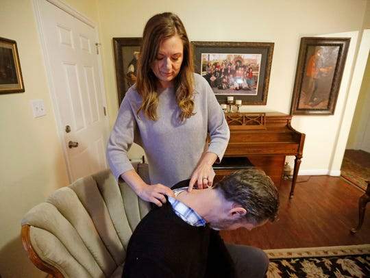 Rebecca Frodsham points to her husband's surgical scars, at their home Monday, April 16, 2018, in Murray, Utah. Nathan Frodsham suffers from cervical arthritis and disc disease.