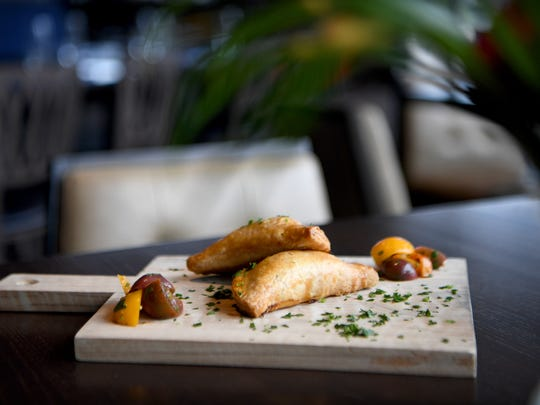 Hemingway's Cuba has two different types of empanadas on their menu, pulled chicken or picadillo ground beef, with a baby tomato stack.