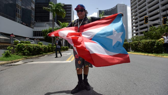FILE - In this Aug. 30, 2017 file photo, a man holds a Puerto Rico flag during a protest against austerity measures as demonstrators march to the offices of a federal control board created by U.S. Congress last year,
