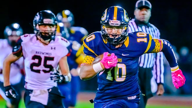 Evan Conn ,10, of DeWitt runs past Ryan Simon ,25, of St. Johns for a 1st down in the 2nd quarter.