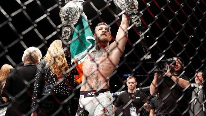 Conor McGregor celebrates with his two championship belts after defeating Eddie Alvarez in their lightweight title bout during UFC 205 at Madison Square Garden.