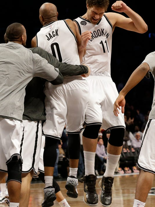 Brooklyn Nets guard Jarrett Jack (0) and center Brook Lopez (11) celebrate after Jack scored the winning goal during the second half of NBA basketball game against the Los Angeles Clippers, Monday, Feb. 2, {year}, in New York. The Nets won 102-100.  (AP Photo/Mary Altaffer)