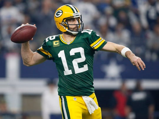Green Bay Packers quarterback Aaron Rodgers (12) throws a pass during the first quarter against the Dallas Cowboys in the NFC Divisional playoff game at AT&T Stadium.