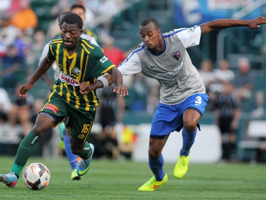 Rochester's Levi Houapeu, left, dribbles past Charlotte's Bilal Duckett during a game June 28, 2014, at Sahlen's Stadium. The Eagles defeated the Rhinos, 1-0.