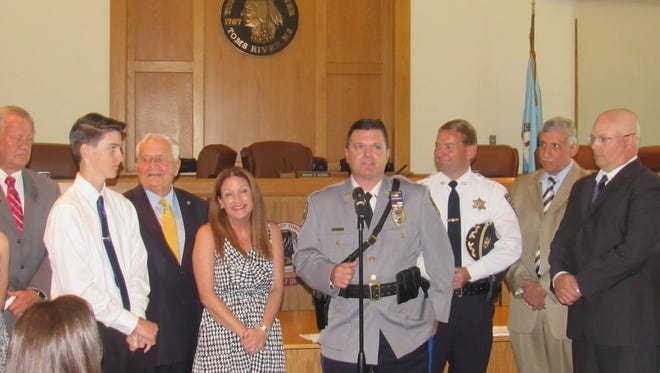 Toms River Police Lt. Chris Anderson (at microphone)  speaks about meeting his wife, Colleen (l), while Monmouth County Sheriff Shaun Golden, Toms RIver Council President Brian Kubiel and former Toms River Officer Daniel Schwester look on.