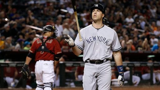 New York Yankees' Mark Teixeira, right, flips the bat in the air after striking out as Arizona Diamondbacks' Welington Castillo, left, walks back to the dugout during the ninth inning of a baseball game Wednesday, May 18, 2016, in Phoenix.  The Yankees defeated the Diamondbacks 4-2. (AP Photo/Ross D. Franklin)