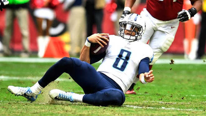 Titans quarterback Marcus Mariota (8) scrambles out of the pocket during the first quarter Sunday.
