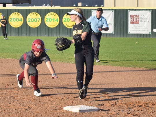 Ouachita's Emma Herring (22, left) makes it back to first as Menard's Morgan Woodard (1, right) looks to catch the ball for the tag.