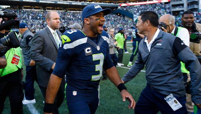 Seattle Seahawks quarterback Russell Wilson (3) walks to midfield to shake hands with members of the Miami Dolphins following a 12-10 Seattle victory at CenturyLink Field.