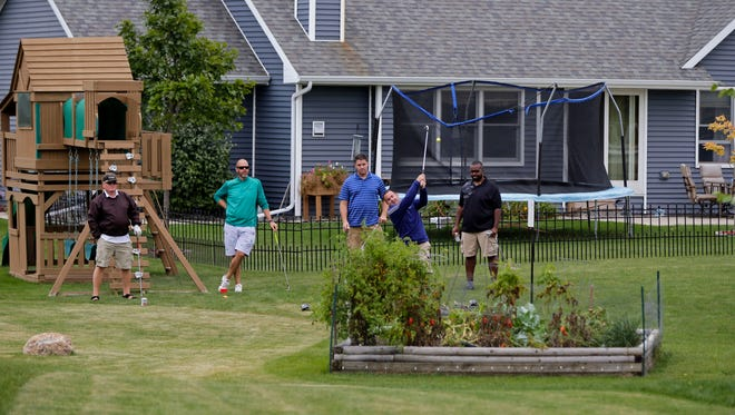 Mark Husen tees off while surrounded by houses, gardens, play equipment and other obstacles as neighbors and friends take part in the fourth annual Barbie Court Golf Invitational Sept. 2 on lawns near Barbie Court in Kimberly.