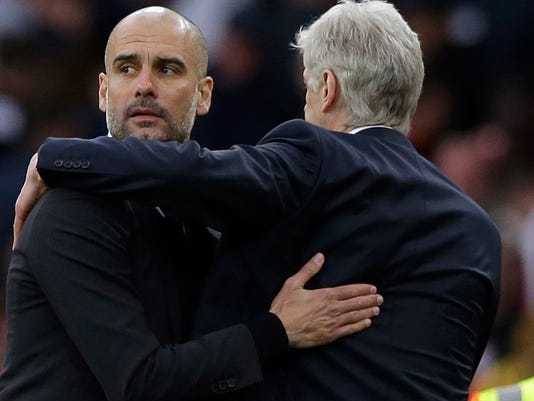 FILE - This is a Sunday, April 2, 2017 file photo of Manchester City manager Pep Guardiola, left, with  Arsenal team manager Arsene Wenger as they embrace each other at the end of the English Premier League soccer match between Arsenal and Manchester City at the Emirates stadium in London. Guardiola's realistic ambitions of capturing the English Premier League title were extinguished weeks ago. Guardiola's last hope of winning silverware in his first season at Manchester City rests with the FA Cup when they play in the semifinal against Arsenal on Sunday April 23, 2017 .(AP Photo/Alastair Grant, File)