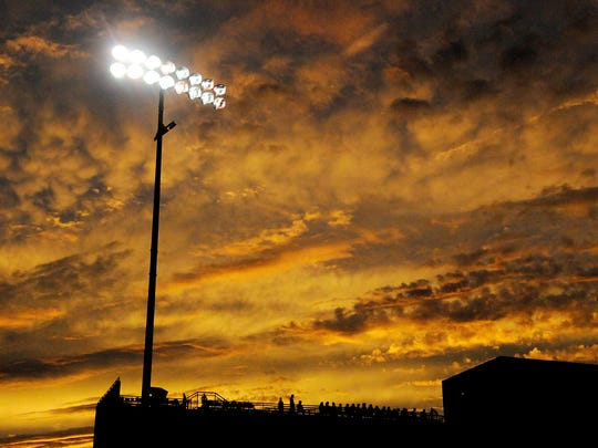 A dramatic sunset lights up the sky behind Husky Stadium during Friday's game between Sartell and Tech.