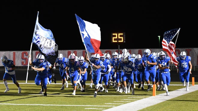 Cedar Creek players storm the field for a game against Rouse.
