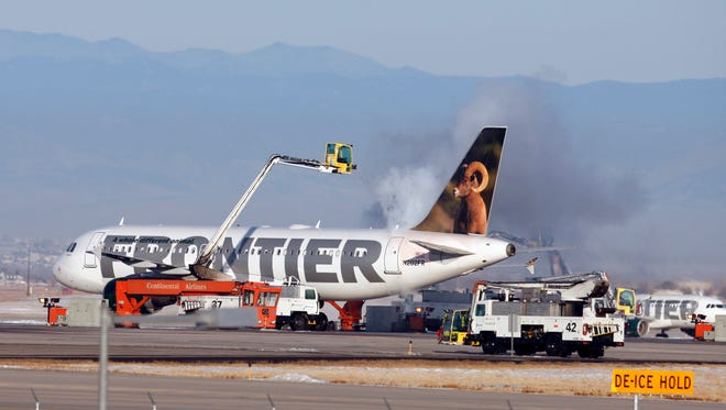 A Frontier Airlines jetliner is sprayed with de-icing fluid before taking off from Denver International Airport.
