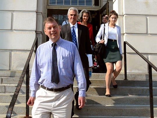 "Front, Malcolm ""Mac"" Parker leaves U.S. District Court in Rutland on Aug. 21 alongside his family and attorney John Pacht after being sentenced by Judge Christina Reiss to 55 months for defrauding hundreds of victims in a Ponzi scheme."