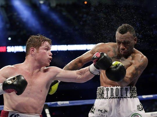 """Boxers Saul """"Canelo"""" Alvarez, left, lands a punch on Austin Trout, right, during the 12th round of a 154-pound title unification bout April 20, 2013, in San Antonio. Alvarez won by unanimous decision."""