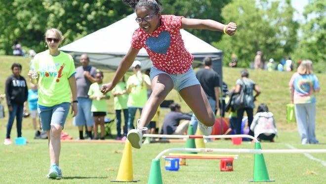 Ahniah Ray, 11, leaps through an obstacle course during Let's Move! at Victor Ashe Park on Saturday, May 7, 2016. The event, promoting healthy eating and outdoor play, is part of a national campaign to fight childhood obesity initiated by First Lady Michelle Obama. (ADAM LAU/NEWS SENTINEL)