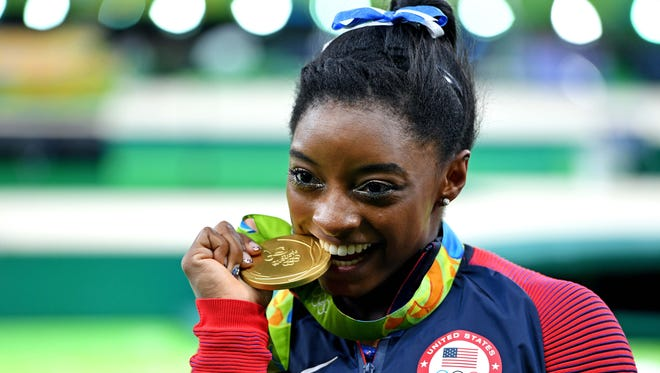Simone Biles celebrates winning the individual all-around gold medal.
