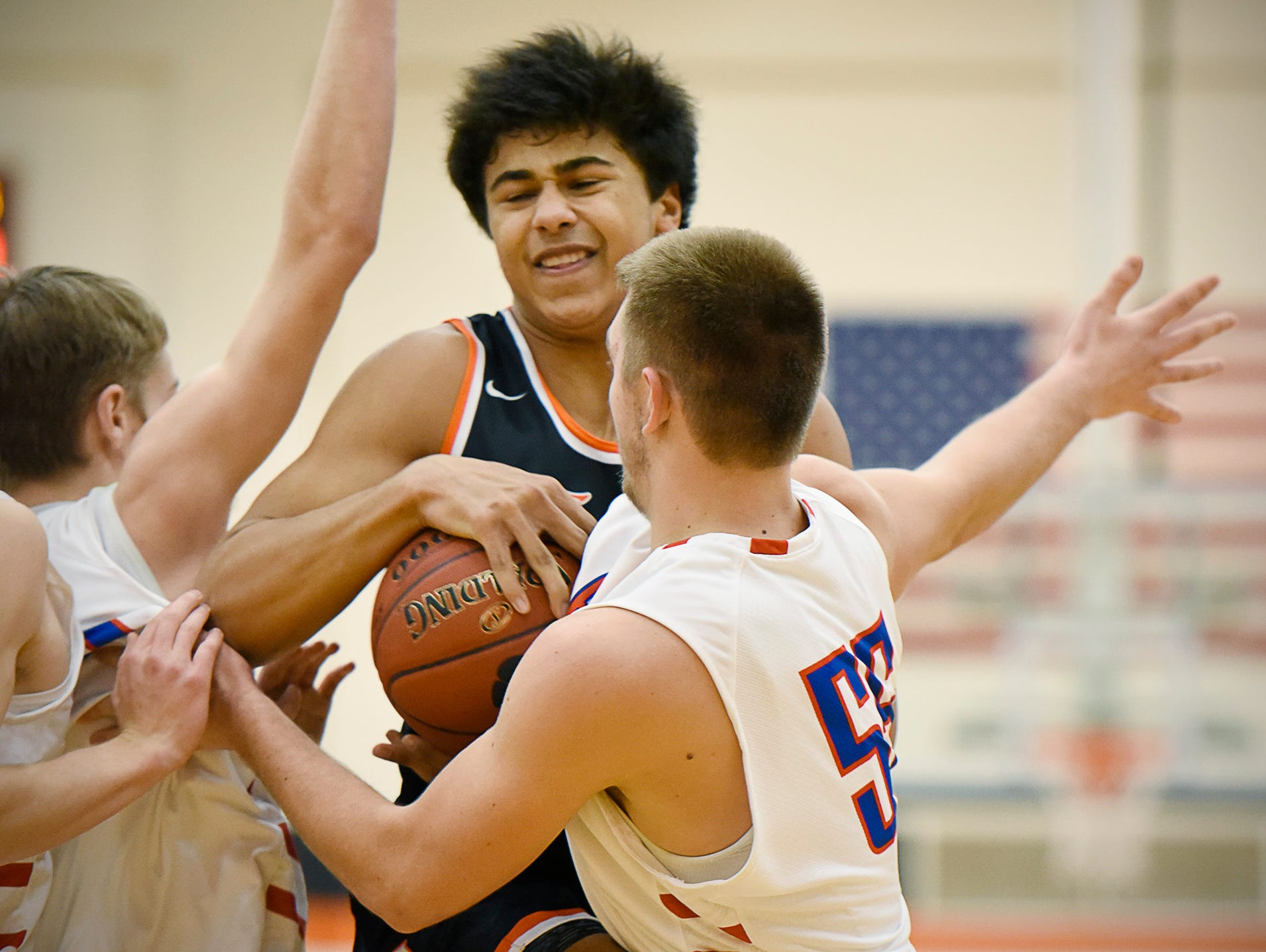 Tech's Brevyn Spann-Ford is shut down by Apollo's Ben Giese (left) and Luke Dunsmoor as he drives in under the basket during the first half Tuesday Dec. 8 at Apollo High School.