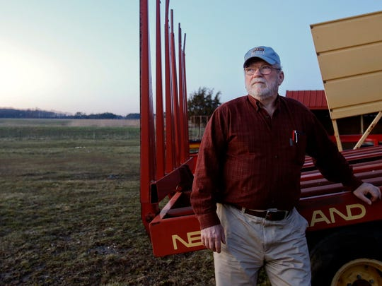 Gary Warren stands with equipment on his 123-acre Port