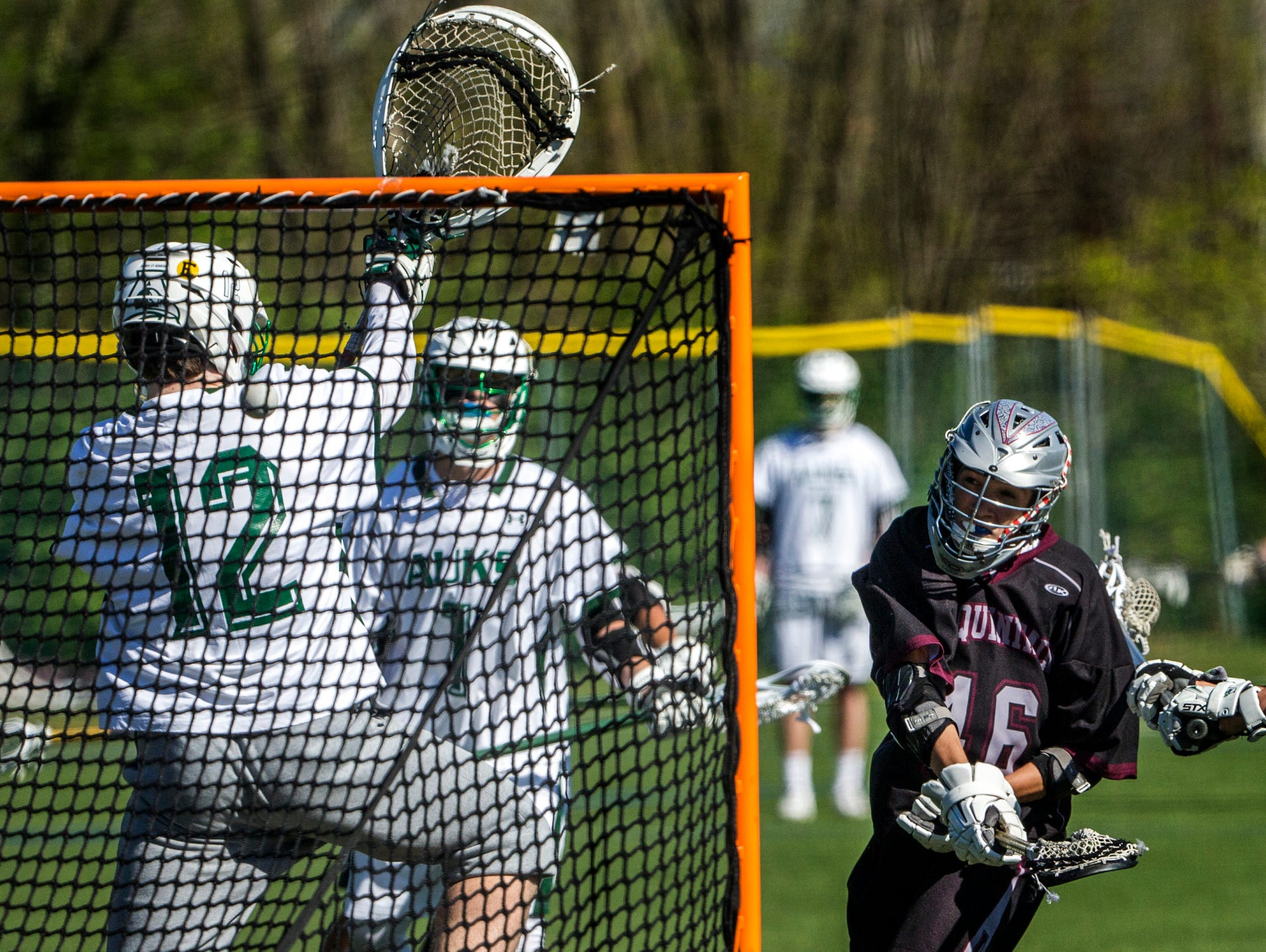 Appoquinimink's John Maloy (right) puts a shot past Archmere goalie Jake Mottola (left) in the first quarter of Appoquinimink's 13-12 win over Archmere at Archmere Academy on Wednesday afternoon.