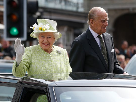 Britain's Queen Elizabeth II waves to the crowds as she rides with Prince Phillip in a open top car to celebrates her 90th birthday in Windsor, England, Thursday, April, 21, 2016. (AP Photo/Alastair Grant)