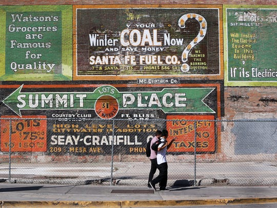 Two children recently walk past old advertising on the side of a building at North Mesa Street and Mills Avenue.