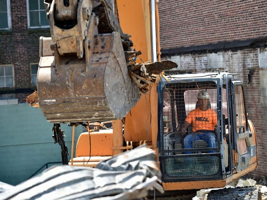Lou Choub, of Neal Enterprises, works in a track hoe as he demolishes sections of the former Central Junior High School on Monday, July 17, 2017. Developer Vern McKissick has plans to transform the building at Queen and Third streets into luxury apartments.