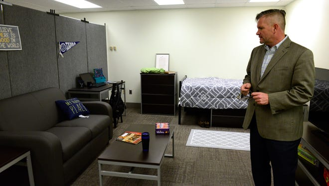 Heath Martin, assistant vice president for student and enrollment services, shows off a mock dorm room at Terra State Community College.