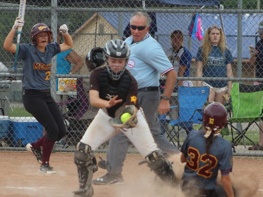 Mercy runner Nicole Belans (32) safely slides across the plate ahead of North Farmington catcher Sara Fish's tag in the pivotal fourth inning of Saturday's district title game.