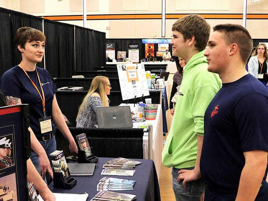 Alex Le Mere, back right, and Hunter Ryczek, front right, students at Oconto Falls High School, speak with US Marine Corps representatives at the SkillsUSA Future Fair held March 1 at Oconto Falls HIgh School.