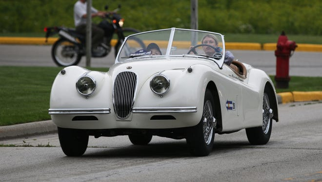 A vintage early 1950s Jaguar is part of a parade route in Wisconsin.