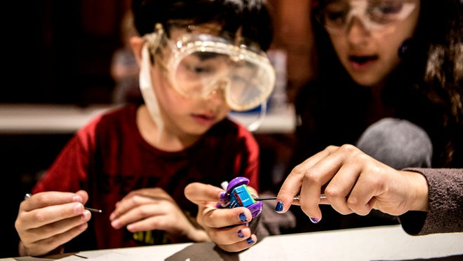 Siblings, Justin and Emma Neugebauer, of Chicago, work on taking apart and putting back together small cars as part of a robotics workshop at the Works during Spring Break.