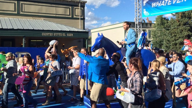 """Revelers at """"Whatever, USA"""" parade down Crested Butte's Elk Avenue on Friday night, led by the fake town's """"mayor,"""" who stars in Bud Light commercials. The brewer is staging a takeover of the town for the weekend as part of an advertising campaign."""