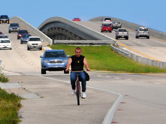 A bicyclist pedals along a newly opened Pineda Causeway