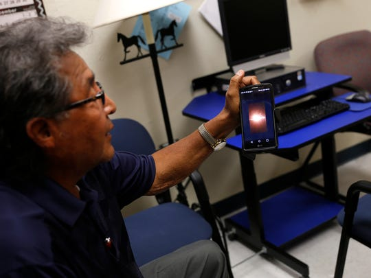 Ervin Chavez, president of the Nageezi Chapter, looks at a cellphone video of a fire burning at a WPX Energy oil production site near Nageezi during an interview on Tuesday at the Dzilth-Na-O-Dith-Hle Community Grant School.