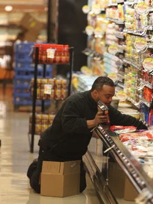 Gus Rivera shelves cheese at the Tops Friendly Markets in Irondequoit in this May photo.