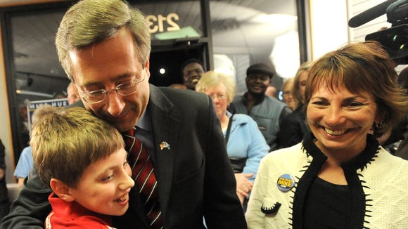 Mike Huether gives his nephew a hug while holding wife Cindy's hand at campaign headquarters on the night of his election as mayor in 2010.