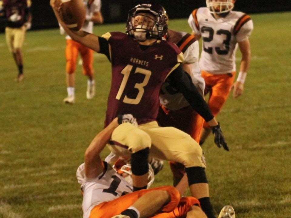 Licking Heights quarterback Gabe Caldwell is tackled by Heath's Aric Adams at the end of the long run Friday during the Hornets' 52-13 victory.