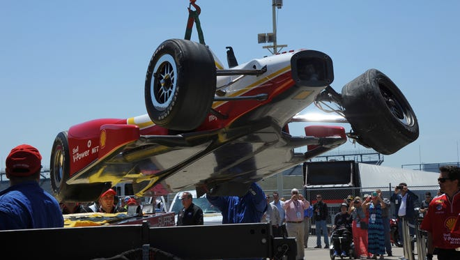 Helio Castroneves's car is brought to his garage after crashing in Turn 1, May 13, at the Indianapolis Motor Speedway.