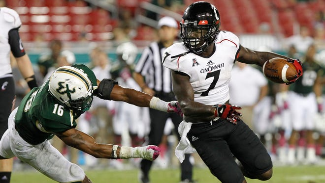 Cincinnati Bearcats running back Tion Green (7) runs with the ball as South Florida Bulls linebacker Reshard Cliett (16) defends during the second half at Raymond James Stadium.