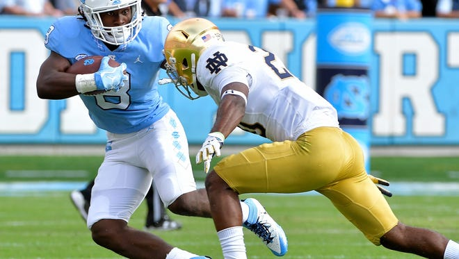 CHAPEL HILL, NC - OCTOBER 07: Michael Carter #8 of the North Carolina Tar Heels runs against Shaun Crawford #20 of the Notre Dame Fighting Irish during the game at Kenan Stadium on October 7, 2017 in Chapel Hill, North Carolina. (Photo by Grant Halverson/Getty Images)