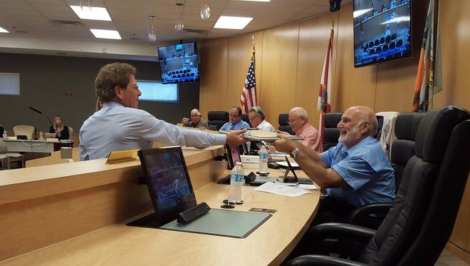 City Manager Roger Hernstadt presents the councilors with a plaque indicating the city's new Class Five community flood rating. The new rating will give residents a five percent increase in their flood insurance discount, which will generate an estimated $500,000 in annual savings.