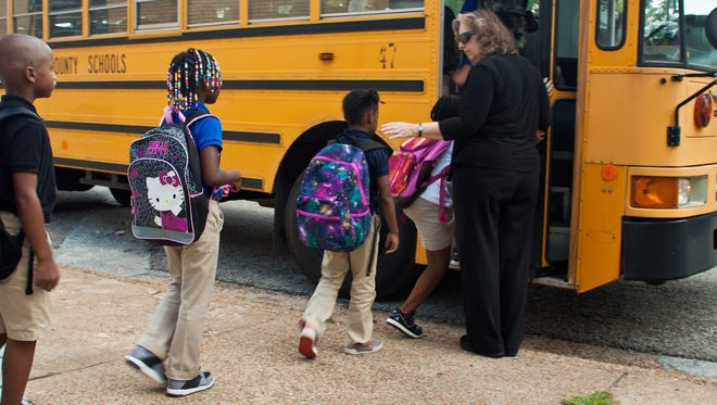 Deborah Frey, the new principal at Alexander Elementary School, helps students get on the bus at the end of the day on Aug. 4.