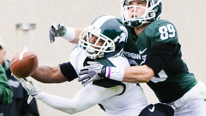 Cornerback Mylan Hicks gets his hands on a pass meant for John Jakubik during Saturday's Green and White game at Spartan Stadium.