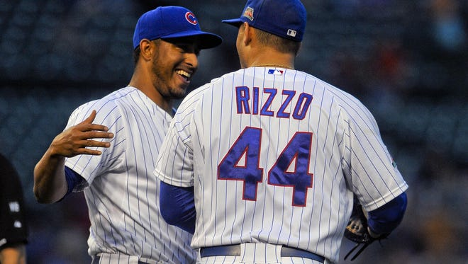 Chicago Cubs relief pitcher Hector Rondon high fives first baseman Anthony Rizzo after beating the San Francisco Giants 2-1 at the end of a rained delayed game at Wrigley Field.